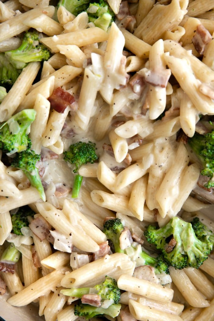 Image of a large pan filled with penne pasta, broccoli florets, and bacon all tossed in an easy homemade cream sauce.