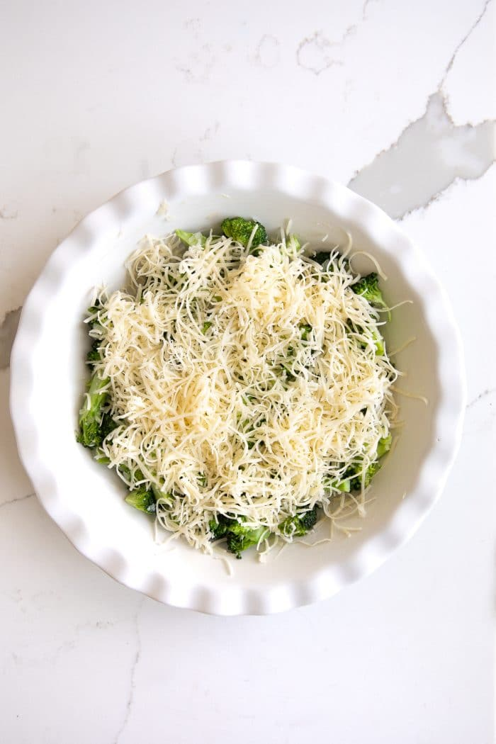 Overhead image of a white pie plate filled with cooked broccoli and shallots and topped with shredded cheese.