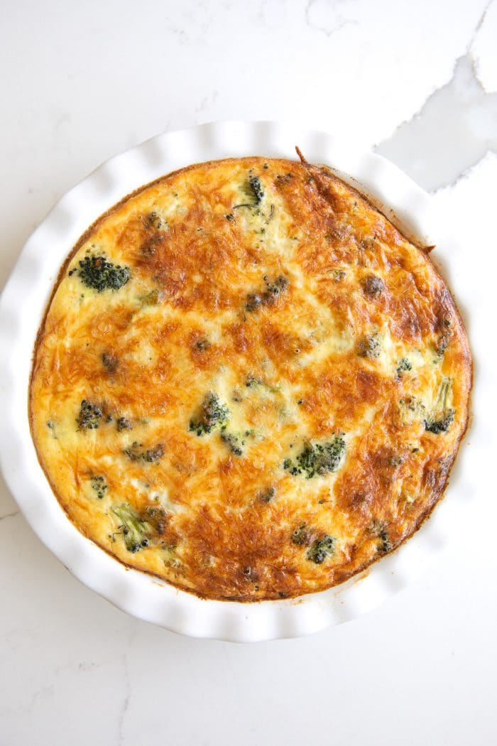 Image of a cooked crustless quiche filled with broccoli in a white pie dish.