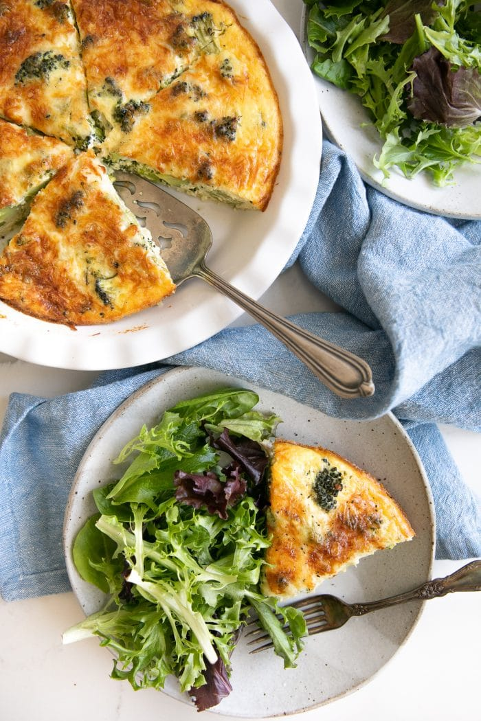 Overhead image of two serving plates filled with a slice of crustless quiche and a side of mixed greens, a blue tea towel, and a white pie dish filled with the remaining quiche.