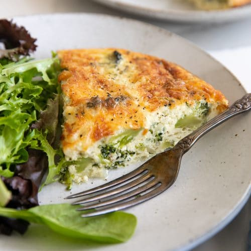 Small serving plate served with a single slice of crustless quiche and a side of mixed green lettuce.