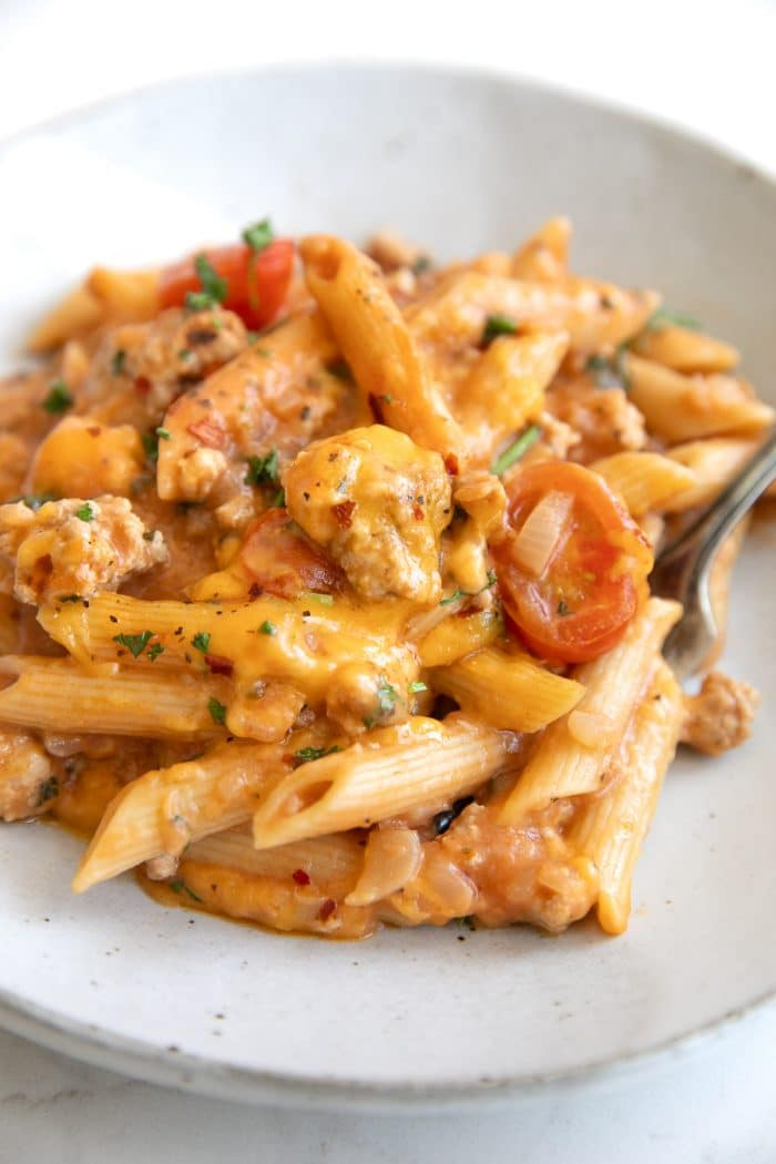 Small dinner plate filled with penne pasta coated in a cheesy creamy tomato sauce and ground turkey.