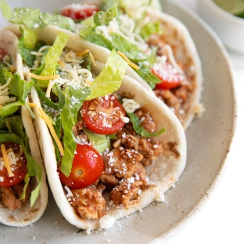 Three ground turkey tacos filled with ground turkey taco meat and topped with tomatoes, lettuce, and cheese, on a small serving plate.