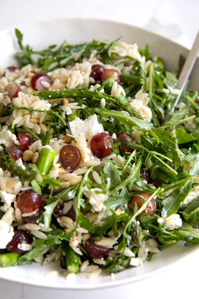 Image of a large salad bowl filled with orzo and arugula salad filled with feta cheese and grapes.