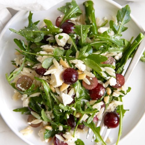 Small white serving plate filled with a salad made with cooked orzo, arugula, asparagus, pine nuts, grapes, and feta cheese.