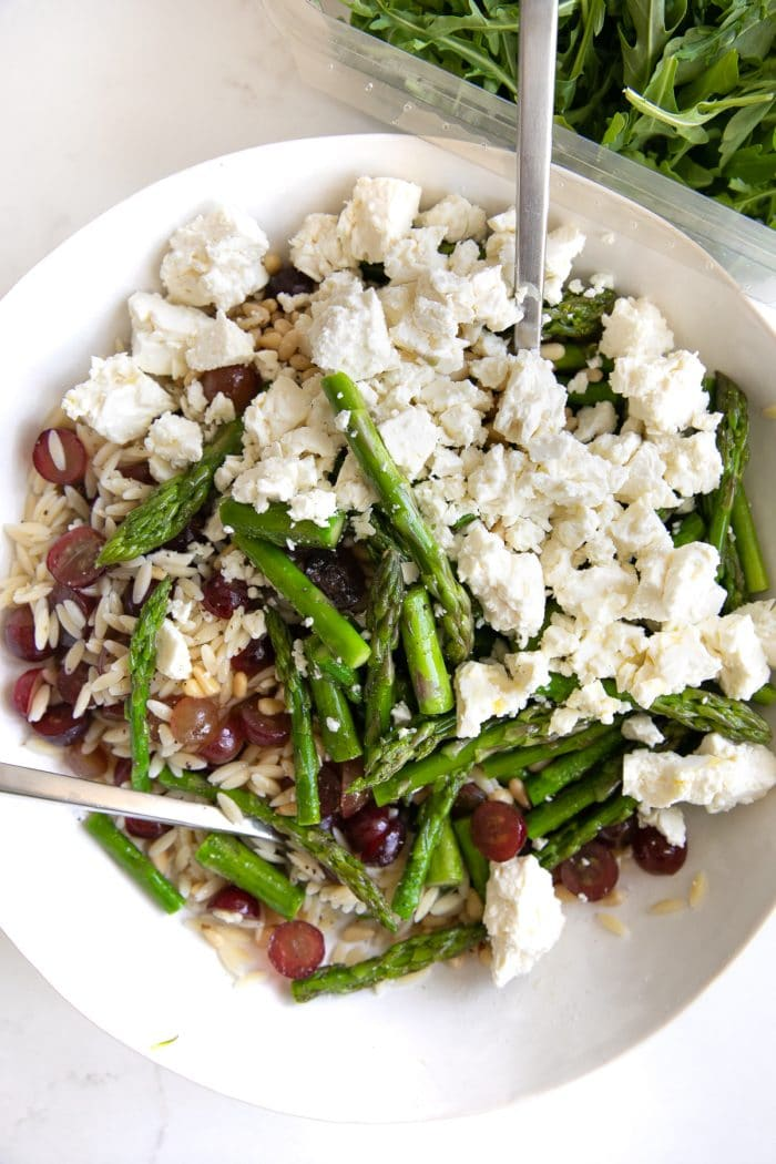Large salad bowl filled with unmixed cooked orzo, arugula, cooked asparagus, pine nuts, grapes, and feta cheese.