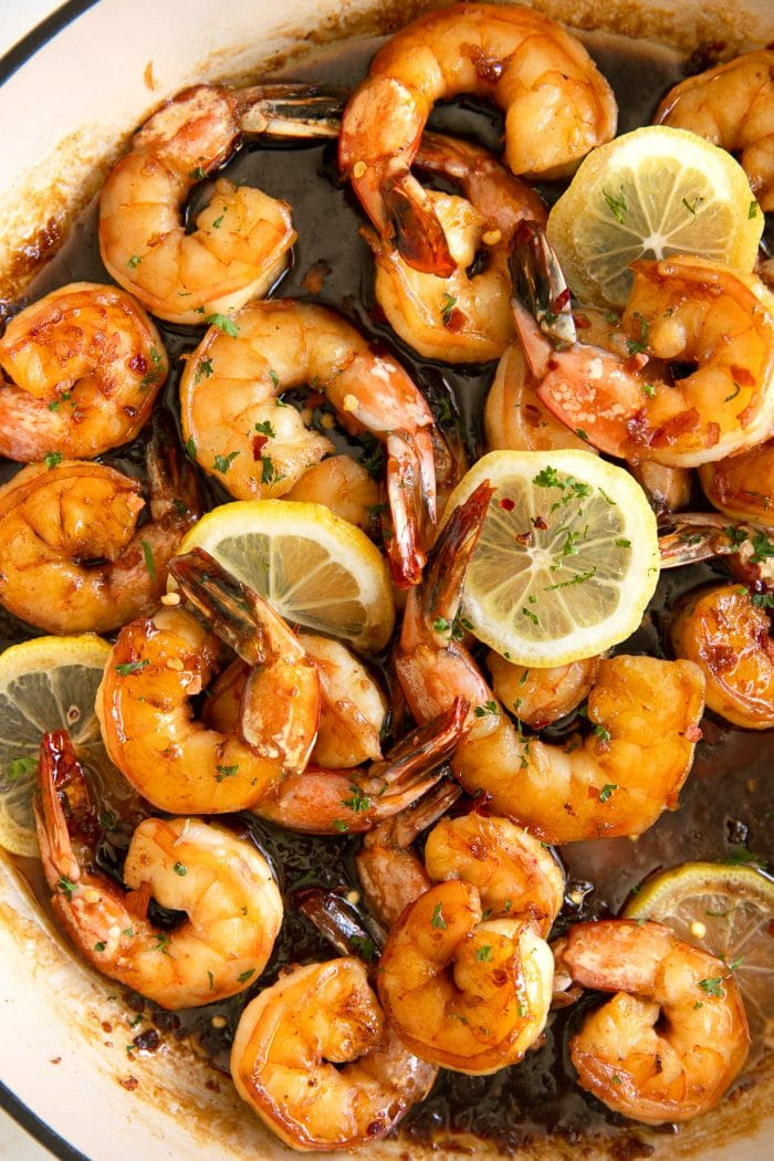Overhead image of a large skillet filled with shrimp simmering in a sweet and tangy honey garlic sauce.