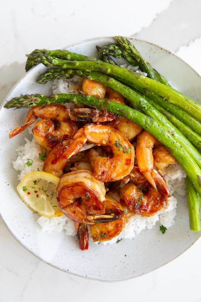 Overhead image of a white plate filled with white rice and asparagus with sweet and tangy shrimp in a honey garlic sauce.