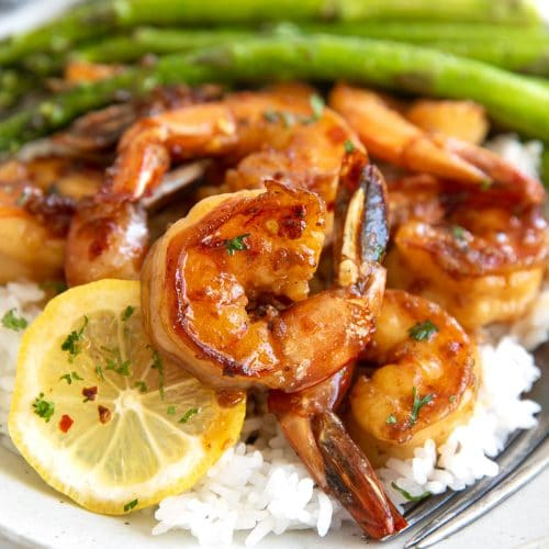 Honey garlic shrimp served with lemon slices set on top of cooked white rice and served with a side of cooked asparagus.