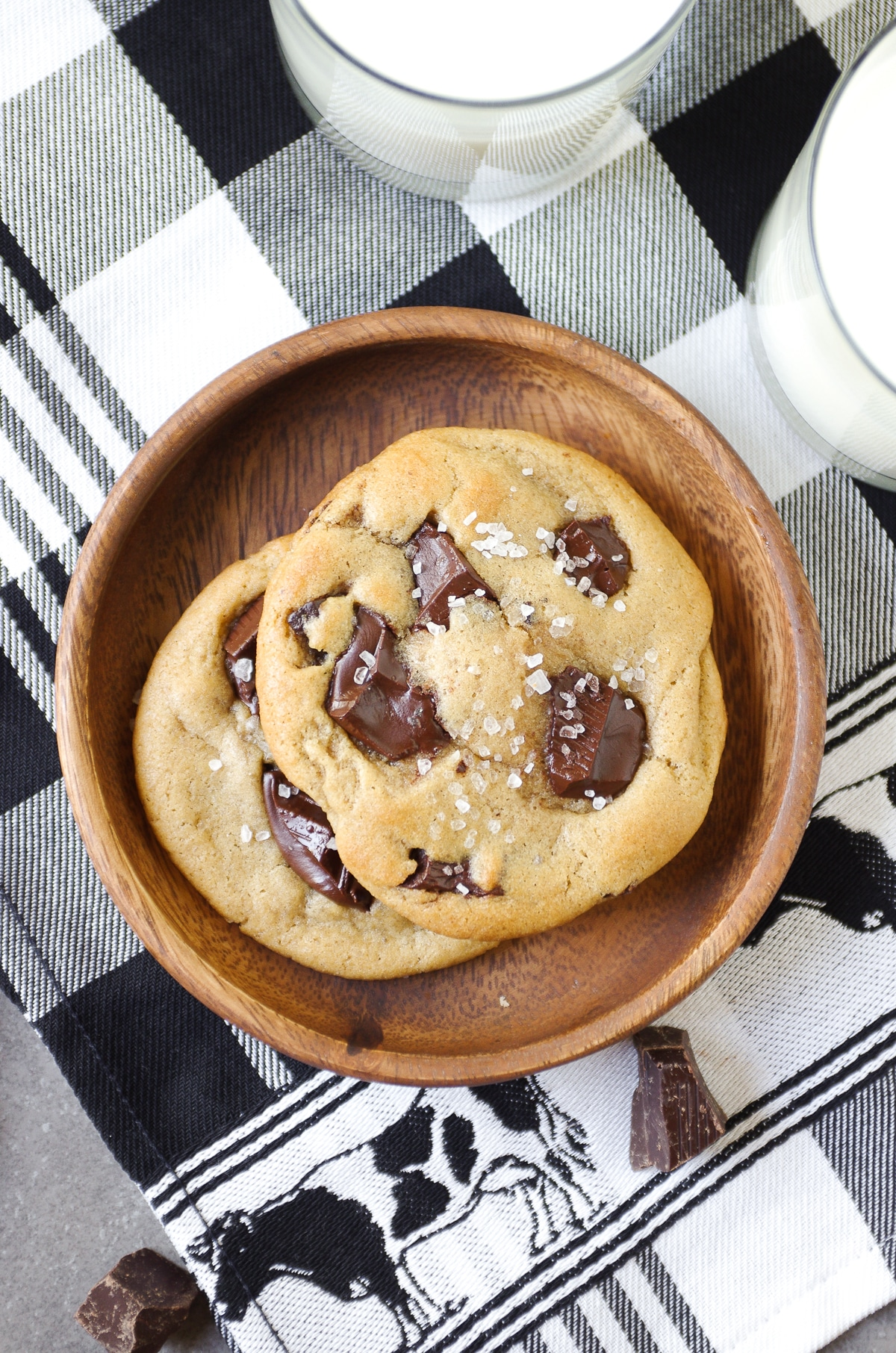 Image of a small wooden plate holding two chocolate chunk cookies topped with flakey sea salt and served with a tall glass of milk.