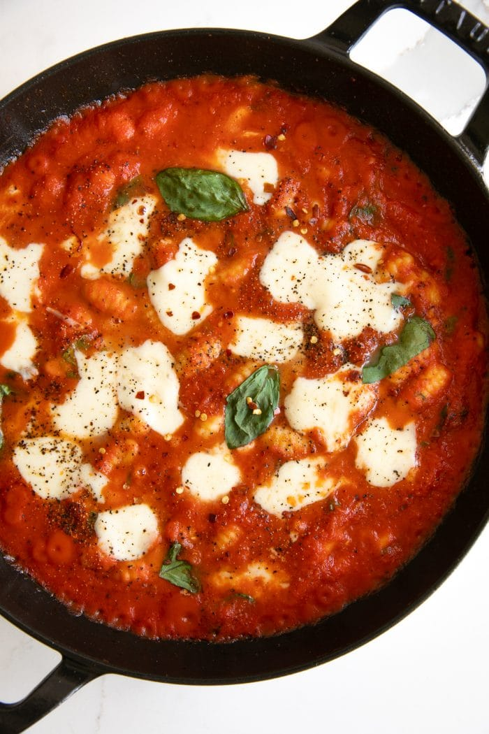 Overhead image of a large skillet filled with gnocchi cooked in homemade tomato basil sauce and topped with fresh mozzarella cheese.