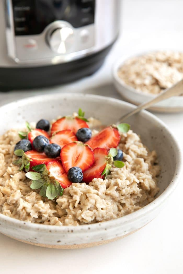 Image of a bowl filled with pressure cooker oatmeal topped with fresh strawberries and blueberries with a pressure cooker in the background.