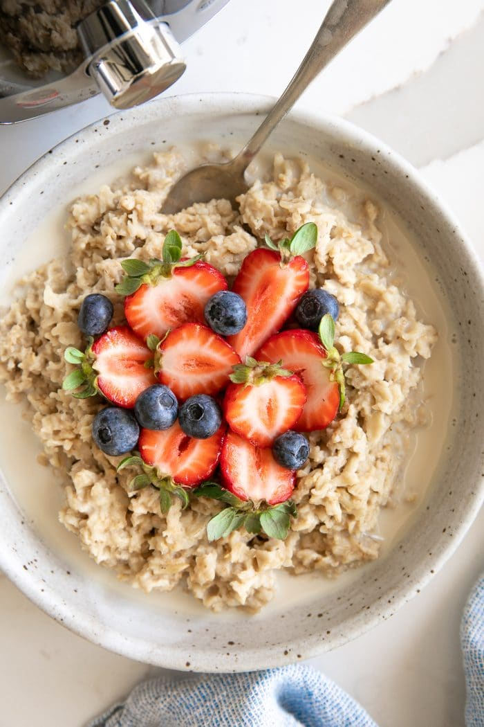 Overhead image of a large shallow bowl filled with oatmeal that's been cooked in the Instant Pot and has been topped with fresh strawberries and blueberries and drizzled with milk.