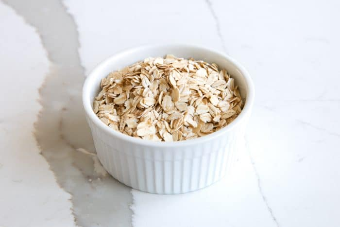 Small white ramekin filled with old fashioned rolled oats.