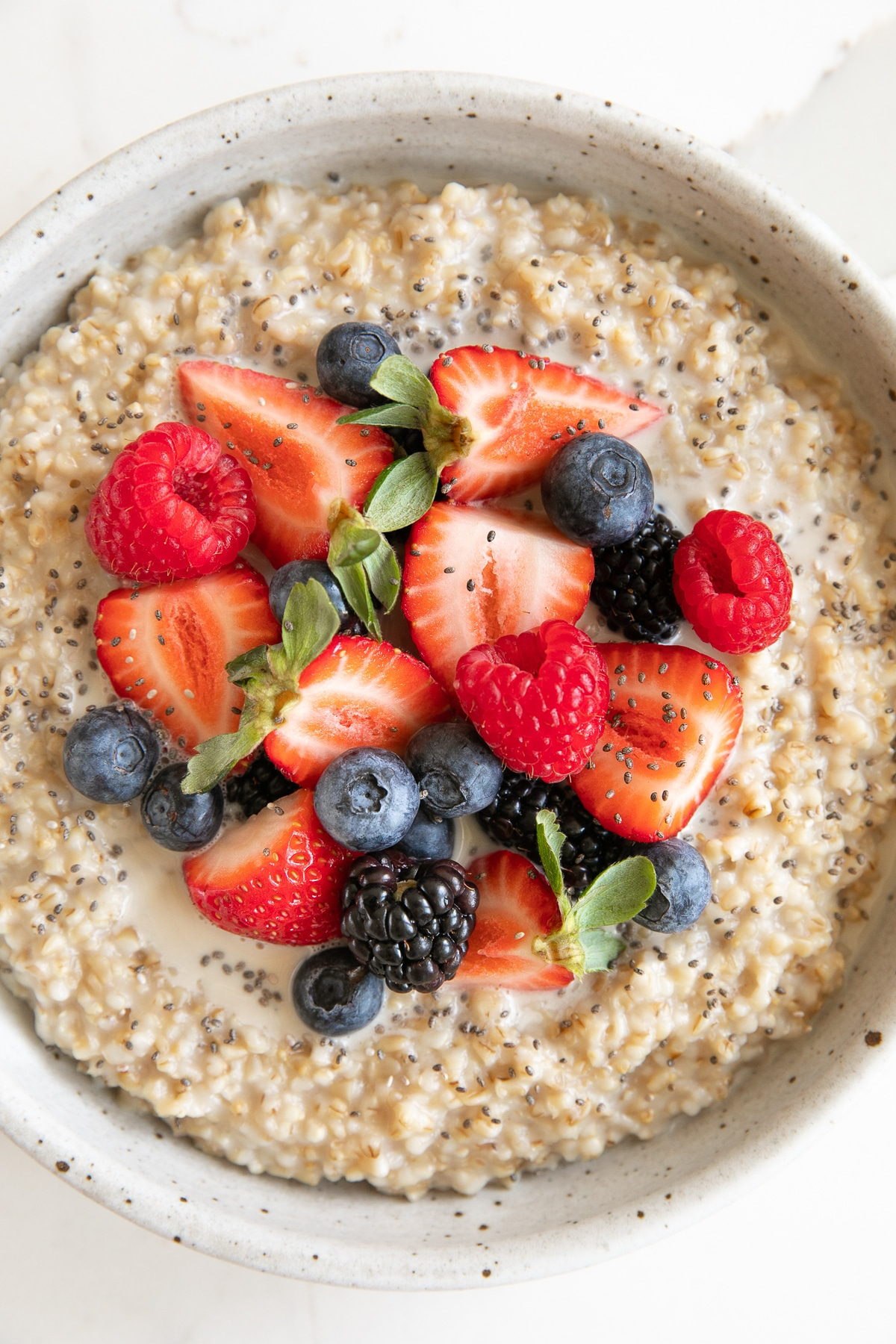 Large round shallow bowl filled with pressure cooker steel cut oatmeal topped with blueberries, raspberries, strawberries, blackberries, and chia seeds.