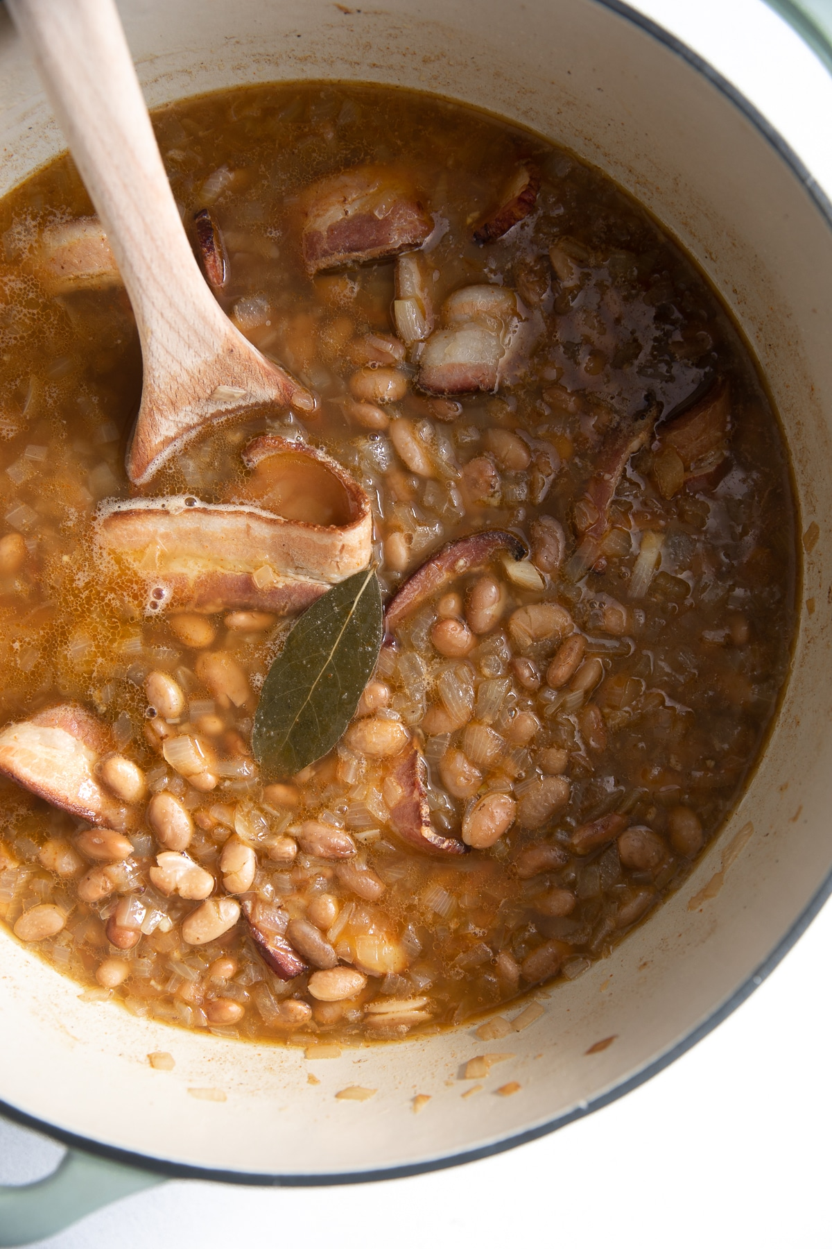 Large pot filled with simmering pinto beans.
