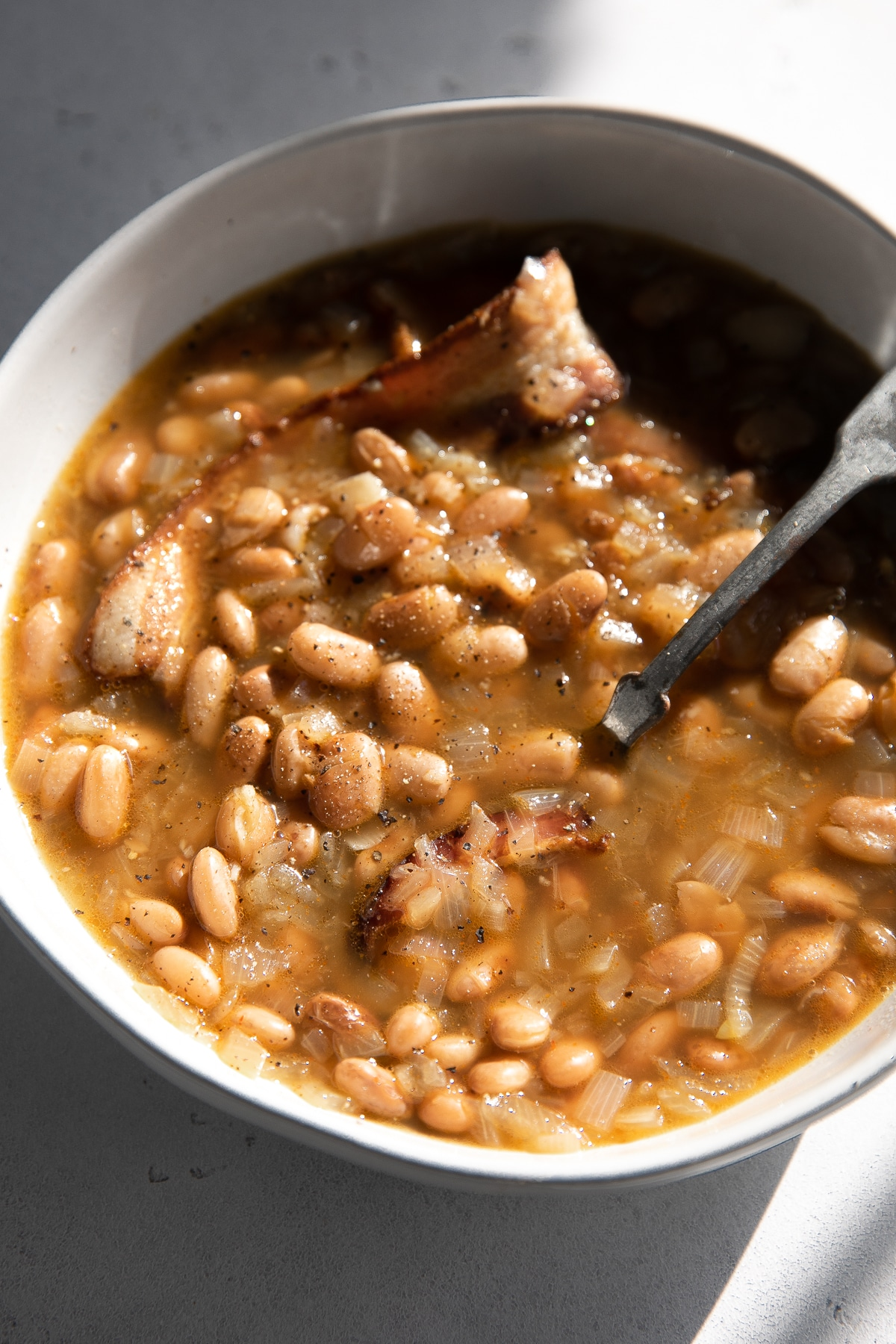 Wide and shallow soup bowl filled with pinto beans simmered with onions, bacon, and herbs.