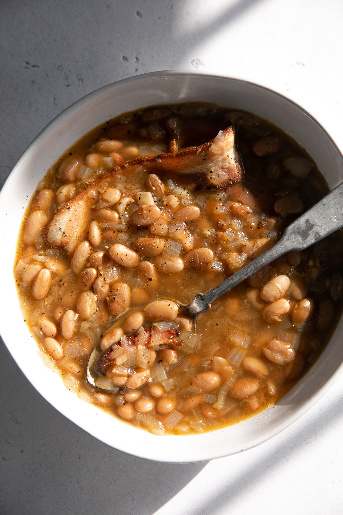 Image of cooked pinto beans with onions and bacon in a light broth.