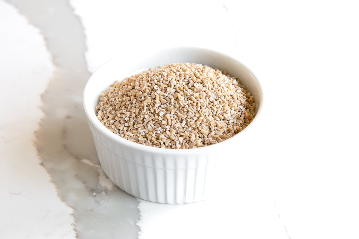 Image of a small white ramekin filled with steel-cut oats.