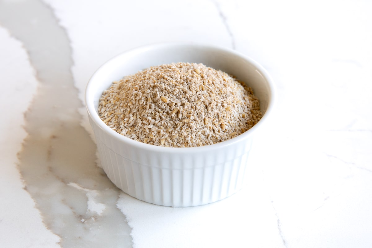 Image of a small white ramekin filled with Scottish oats.