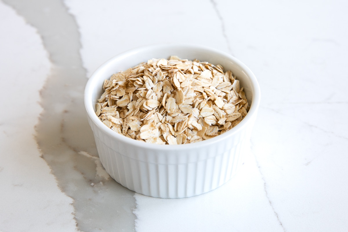 Image of a small white ramekin filled with old fashioned rolled oats.