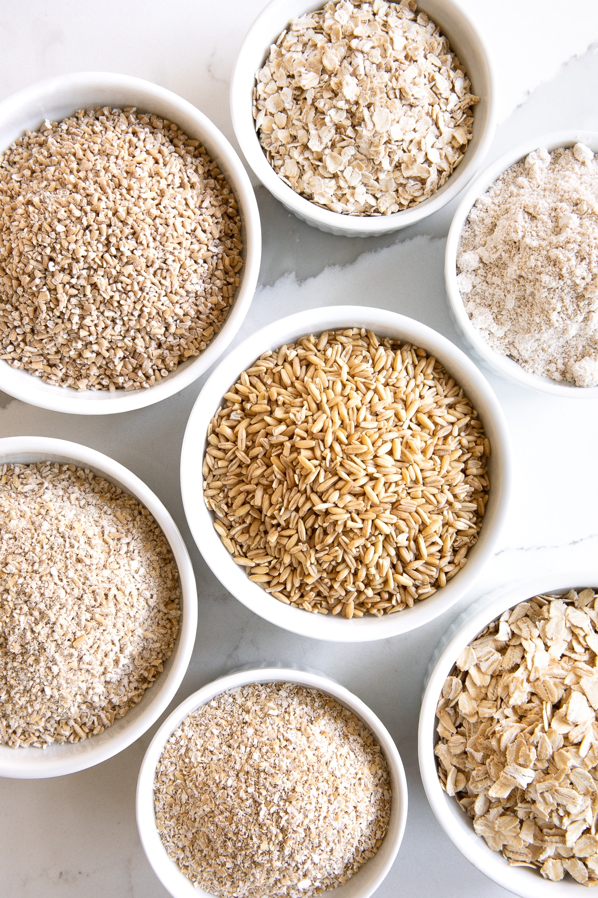 Small white ramekins filled with the different kinds of oats including rolled oats, groats, instant oats, steel-cut oats, scottish oats, oat bran, and oat flour.