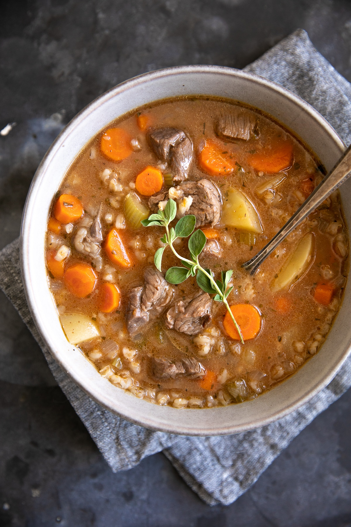 Overhead image of a large soup bowl filled with beef barley soup topped with fresh oregano.