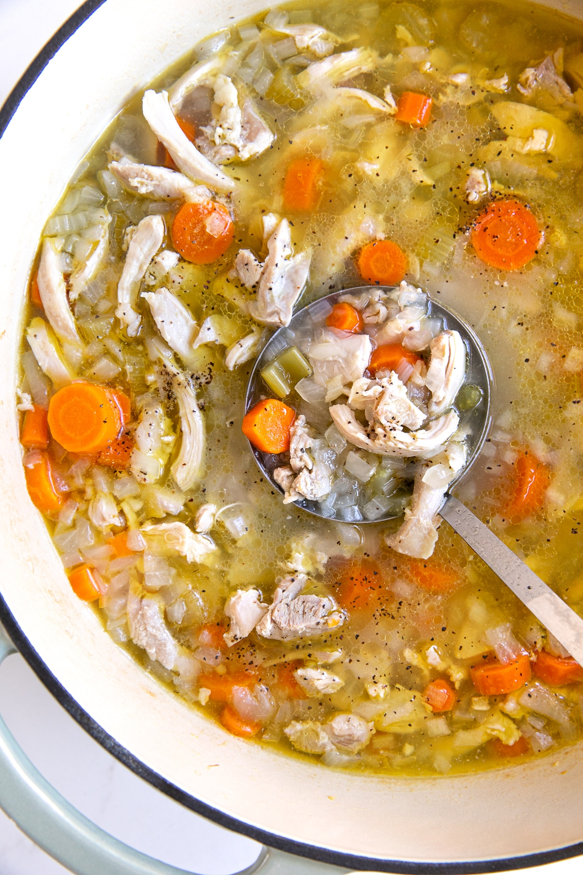 Overhead image of a large Dutch oven filled with homemade chicken and barley soup filled with carrots, celery, and onions.
