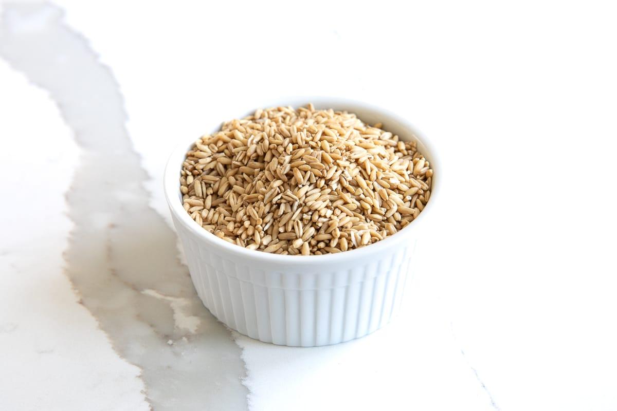 Small white ramekin filled with oat groats.