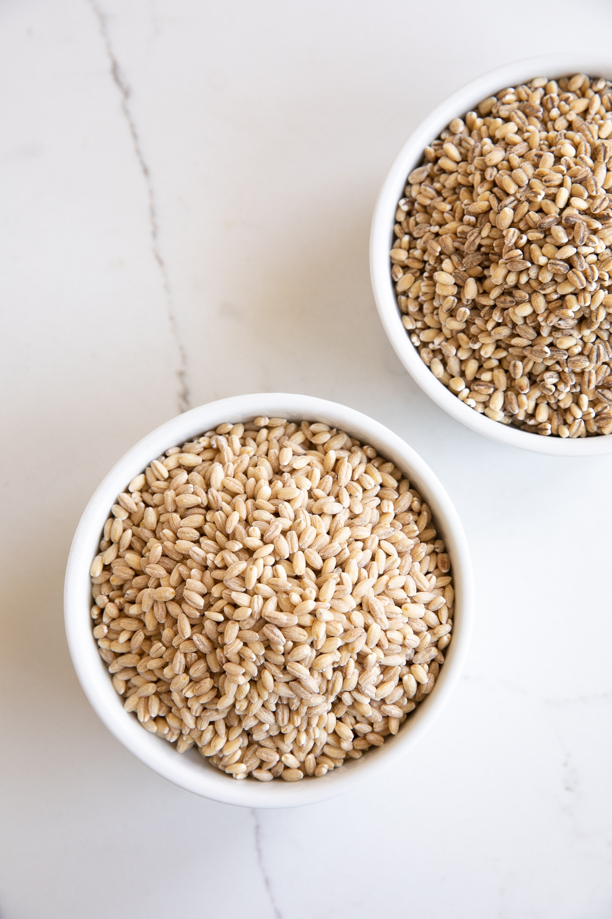 Image of two white ramekins one filled with pearled barley and one with hulled barley.